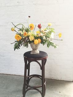 Wild Green Yonder | Yellow citrus and poppy floral arrangement in stone urn