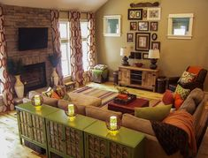 A Warm Living Room Featuring Green And Orange Earth Tones Patterned Curtains Rustic Wood