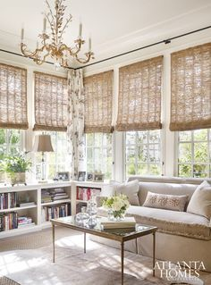 Neutral, half wall corner bookcase, woven window shades, ornate gold chandelier
