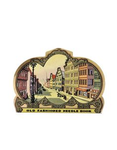 """From their debut in the late 19th century until the 1950s, humble sewing-needle books were also wonderful little works of art that depicted subjects ranging from women shopping together, household objects, buildings and townscapes to such contemporary milestones as the advent of dirigibles. Pictured: This purse-shaped needle book features an """"old-fashioned"""" townscape depiction."""