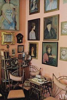 Portraits by Belgian, American, French, Russian, and Canadian artists decorate a salmon-walled dining room in costume and set designer Alexandre Vassiliev's Vilnius, Lithuania, home | archdigest.com