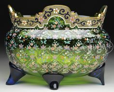 MOSER DECORATED BOWL. Moser green glass bowl has colorful enameled stylized flowers surrounding the bowl with a gold coraline band surrounding the lip. Band is further decorated with enameled flowers and scrolls. Vase is finished with four applied cobalt blue feet.