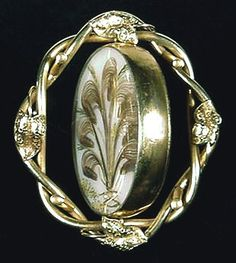 "PLUMES OF PASSING ( Victorian Mourning Jewelry Swivel Brooch ): Grand in size, glorious in execution, this Victorian revolving (or swivel) brooch is simply stunning. (c. 1850 - 1860) Extremely desirable to collectors, this example of palatte-worked ""Prince of Wales"" feathers on milk glass is perfection. The seven hair plumes are a light brown in color. When you revolve the central plaque, the reverse side reveals a hand-colored tintype of a very dramatic gentleman."