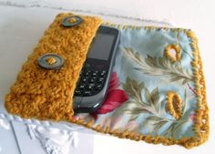 Crochet Cell Phone Case - used a similar yellow yarn, maroon cloth inside and green buttons. I also made it large enough to hold phone, iPod, some cards and a small set of keys.