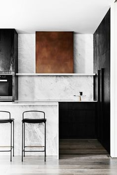 Minimalist kitchen with marble countertops, a brass stove hood, and black leather barstools
