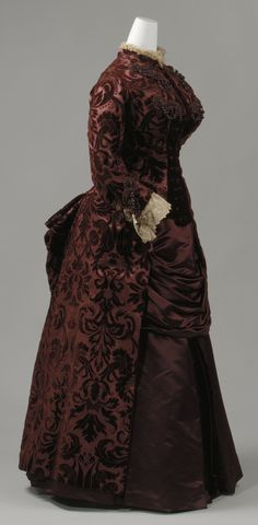 """Dress, by Worth, 1883-85. Metropolitan Museum of Art. The Met: """"Lavish textiles were not only used for evening wear in Worth's designs, as this day dress of cut and uncut voided velvet attests. The ensemble also provides an example of Worth's practice of incorporating elements of historic dress in his designs. The large scale of the pomegranate and floral motif follow the style of Louis XIV textile patterns... A day dress like this would have been appropriate for walking or making social…"""