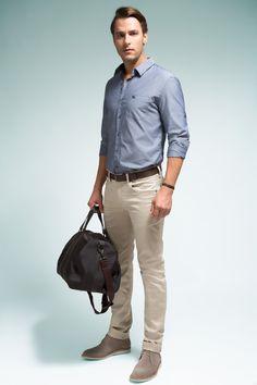 Camisa com microestampa e aspecto denim, calça cáqui five pockets, bota de camurça e mala de nylon para as viagens rápidas.