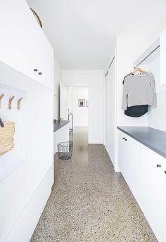 These 4 laundry layouts are filled with clever ideas Laundry: Terrazzo floors make the white galley-style laundry pop. A hanging rail above allows for additional storage, and ample cabinetry provides even more space. Utility Room Designs, Terrazo, Modern Laundry Rooms, Laundry Room Shelves, Laundry Room Inspiration, Terrazzo Flooring, Concrete Floors, Hanging Rail, Laundry Room Design