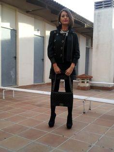 outfit isabella con chaqueta de cuero de la coleccion instinto, modelo instinto. Vestido de rayas en piel sintética, zapatos de plataforma y colgante de plumas naturales  diseño de la colección capricho´s by isabella mas bolso de Chanel, un total look en color negro!!
