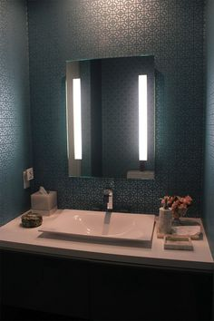 Restroom with iluminated mirror and Designer´s Guild wallpaper.