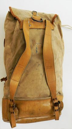 "Rugged Vintage Leather and Canvas Backpack. Very nice thick leather base with heavy duty khaki canvas body. Thick leather backpack adjustable straps with wool padding. Drawstring closure with deer antler pull tab. Heavy duty buckles and D ring. Inside has canvas sectioning for organizing items. Measures 20"" tall, 14"" across and 5.5"" deep."