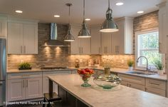 Contemporary Kitchen with Multiple Refrigerators, Simple marble counters, Kitchen island, Full overlay cabinets, Wall Hood