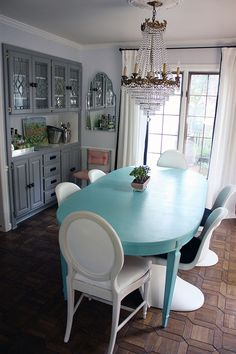 Charmaine & Mark's Lovely, Lively Family Home. Turquoise dining table with mismatched white chairs. Crystal chandelier.