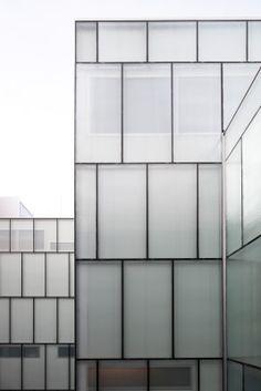 Hinter der vorgehängten Glasfassade ist die tragende Wand des Neubaus sichtbar