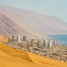 The coastal city of #Iquique built on the desert sands of the Atacama Desert in #Chile. The long sand dune in the foreground is the tail of Cerro Dragón (Dragon Hill). According to the 2012 census Iquique has a population of roughly 180600 people. Photo by Mike Theiss @ExtremeNature by natgeotravel