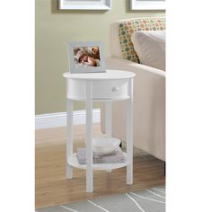 The Altra Furniture Round End Table features a small drawer and lower shelf for storage and is designed in a beautiful painted-white finish to enhance your home's style. Perfect to use as an end table or nightstand.