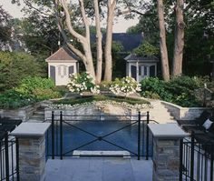 Two large oak trees dictated the symmetrical design of this backyard.  Classic architectural details ~Two pavilions draw the eye outward from the house. A gravel area with bistro table is a casual spot to snack after a swim, with comfortable lounge chairs flanking each side of the pool. In the foreground, an upper terrace offers a more formal dining area for entertaining.