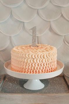 Ombré Cake: For a sweet silver and peach first birthday party, party-goers were treated to an ombré cake with a sparkly number one.  Source: All the Frills