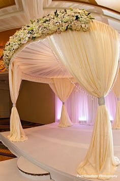 The neutral palette of White/Ivory florals paired with a romantic chiffon draped Chuppah, embellished with hanging crystals and orchids. Wedding Stage, Dream Wedding, Arch Wedding, Wedding Canopy, Ceremony Decorations, Wedding Centerpieces, Pipe And Drape, Chuppah, Event Decor