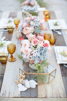 Centerpiece designed with natural elements, geodes, quartz, reclaimed wood, grape branches, gold trimmed glass cases, peach garden roses, neon twine, dusty miller and air plants.