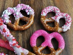 An easy dessert for kids, pretzel twists and rods dipped in pink candy melts then decorated with Valentine's Day hearts and candy sprinkles.