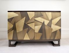 Design & Finish A striking and unique sideboard, in an original design by Rupert Bevan Ltd. Constructed in walnut with a stained and lacquered finish, the doors are panelled with interlocking brass tiles in varying degrees of patination to create an unusual angular effect. Geometric base and handles in dark patinated brass. Interior of cabinet …