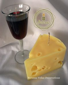 Vela con forma de queso acompañada de una vela de cera gel en copa de vino.
