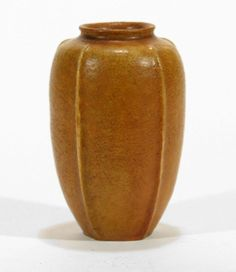 c.1900   Grueby Pottery matte ochre or butterscotch color vase with five stem like ribs that swell slightly at the top resembling buds. It has a very pleasing form with a fine lip and the ribs start at the bottom and stop just over the shoulder. The glaze is thick and nicely textured and thins on the high points. It measures 4 7/8 inches by 3 1/4.