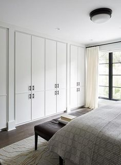 Modern brown and gray bedroom is fitted with a wall lined with white closet cabinets contrasted with matte black pulls.
