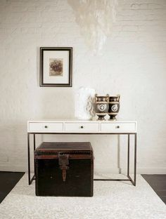 White piano lacquered console table with brass lined drawers, antique brass frame base, vellum parchment front drawer detail and brass pull knobs.
