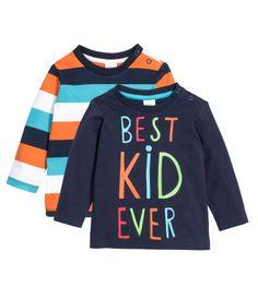 Camisetas de manga larga en punto de algodón, una estampada y una con motivo en la parte delantera. Botones de presión en un hombro.