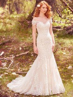 Maggie Sottero - MARCY, This romantic fit-and-flare wedding dress features cascades of lace appliqués that trim the illusion sweetheart neckline, illusion off-the-shoulder sleeves, and illusion low back with keyhole opening. Complete with exquisite hemline of lace appliqués. Finished with covered buttons over zipper closure.