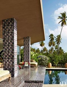The poolside terrace is clad in tile designed by Mota | archdigest.com