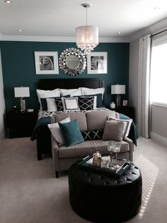 Bedroom with a beautiful green or teal feature, accent wall and black accents.