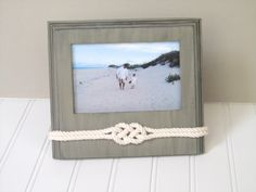 """Beach Photo Frame - Sailors Knot - Nautical Rope Decor. I hand tied a decorative knot using 3/16"""" (.5 cm) diameter cotton rope and securely attached it to a picture frame. It is to be displayed in a landscape position on a tabletop and holds a 4x6 photo.    • Outside edge of frame: 7"""" x 8"""" (17.8 x 20.3 cm)  • Inside edge of frame: 3.5"""" x 5.5"""" (8.9 x 14 cm) ~ 4 x 6 photo  • Center Knot: 1.75"""" x 1 (4.4 x 2.5 cm)  • Easel back frame    Perfect for displaying your beach vacation photos! Plea..."""