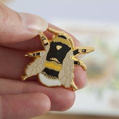 A beautiful British Bee Pin. A hard enamel pin, based on an illustration of a British White-Tailed Bumble Bee. Pop it on your collar, bag or coat to jazz up your outfit! Show your love for the British Bee, it needs your help! Presented on a backing card, this pin measures 3 cm across, and is made from shiny gold metal with black, white, yellow and peachy enamel highlights. This pin has a butterfly backing. The pin is made from hard enamel, so its nice and sturdy. Backing card measures H…