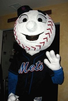 This costume is homemade, it was made with a 30 inch beach ball and paper mache then panited white. The nose was formed with clay and the eyes are made of vinyl. The eyebrows are styrofoam and the stiches are red ribbon that I cut and glued. The hat and the jersey are store bought but on the back of the jersey I ironed on letters that say Mr. Met and his number which is double zero. His gloves I sewed white fleece fabric together and stuffed. He also has white baseball pants with black socks…