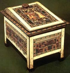 The Tomb of Tutankhamen: This chest was found in the Annex. It had already been ransacked in antiquity. Originally it probably contained king's clothing. Made of a red wood, almost every part of the outer surface is richly decorated. In the center, surrounded by borders of stained ivory, is a scene depicting the king and queen in the marshes. Bordering the scene on three sides are several separate floral groupings.