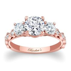This unique rose gold, three stone diamond  engagement ring features a cathedral shank and three prong set round diamonds across the center, shared prong set diamonds grace the shank for an added touch of elegance. <br /> <br /> Also available in yellow, white gold, 18K, Platinum.