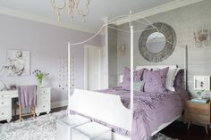 Purple and gray teen girl's bedroom features an accent wall clad in platinum gray grasscloth lined with a gray sunburst mirror over a white canopy bed dressed in purple floral bedding flanked by small mid century modern nightstands illuminated by French wall sconces alongside a pair of silver metallic faux python cube stools placed at the foot of the bed atop a gray shag rug.