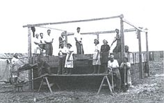 Here we see a sod house being built by tamping the sod.
