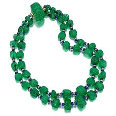 An important carved emerald, diamond and sapphire necklace the double strand composed of fifty-one irregular melon-carved emerald beads, measuring approximately 22.2 x 13.7 to 8.0 x 7.5mm., spaced by round brilliant-cut diamond rondelles and tumbled sapphire beads, completed by an emerald bead clasp
