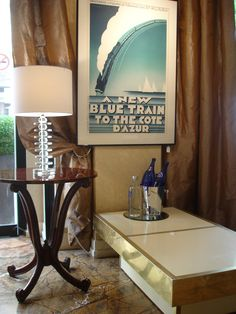 Mix of style: Art Deco poster with small table, vintage coffee table and contemporary lamp.