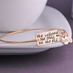 """Each bangle is hand formed from sterling silver wire and then hand-hammered and tumbled for shine and strength. A stainless steel rectangle measuring 1 inch across is engraved with the words """"she beli"""