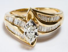 "Lot 267: 10k Gold and Diamond Ring; Having a marquis cut diamond surrounded by white gold and flanked by baguette cut diamonds running down the band; marked ""10k"" inside band"
