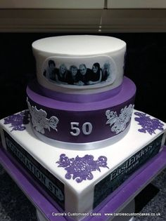 A purple and white 50th birthday cake with printed edible images and cake lace.
