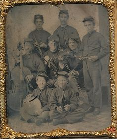 Sixth plate tintype of a regimental band as they ready to play some dancing music. Most likely from one of the many Irish regiments but their actual identity is unknown. There are a total of 8 band members all holding various instruments. The two men in the far back are holding clarinets. The two men in the center playing violins are flanked by a flute player and a fellow playing the chello. (Continued in comments.)