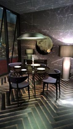 Dining room interior design with herringbone tile floor and marble wall or wallpaper. Dark room - moody!