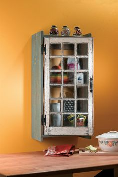A reclaimed window made into a rustic kitchen cabinet