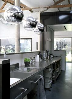 kitchen put together with free-standing pieces for an industrial feel and classed-up with some great light fixtures